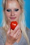 Blonde Frau, die eine Tomate isst Lizenzfreies Stockfoto