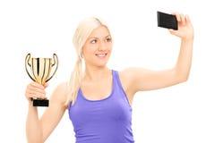 Blonde Frau, die eine Trophäe hält und selfie nimmt Stockfoto