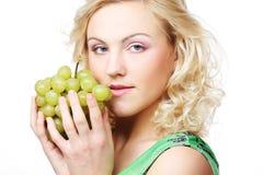 Blonde Frau, die eine Weintraube hält Lizenzfreies Stockbild
