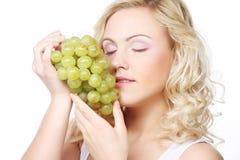 Blonde Frau, die eine Weintraube hält Lizenzfreie Stockfotografie