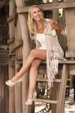 Blonde Frau, die in einem Baumhaus sitzt Lizenzfreie Stockfotos