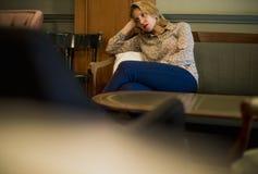 Blonde Frau, die an einem Café wartet Lizenzfreie Stockfotos