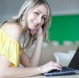 blonde Frau, die an einem Laptop arbeitet Stockfoto