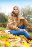 Blonde Frau, die in einem Park sitzt Lizenzfreies Stockbild
