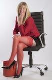 Blonde Frau, die in einem schwarzen vollziehendstuhl sitzt Stockfotos