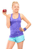 Blonde Frau, die einen köstlichen roten Apfel hält Lizenzfreie Stockbilder
