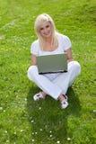 Blonde Frau, die einen Laptop auf dem Gras verwendet Stockfoto
