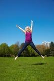 Blonde Frau, die in einen Park springt Lizenzfreie Stockfotografie