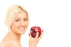 Blonde Frau, die einen roten Apfel hält Stockfoto