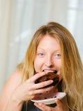 Blonde Frau, die einen Schokoladenschokoladenkuchen beißt Lizenzfreie Stockbilder