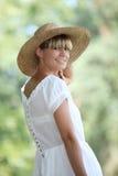 Blonde Frau, die einen Strohhut trägt Lizenzfreie Stockbilder