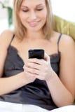 Blonde Frau, die einen Text sitzt auf einem Sofa sendet Stockfotos