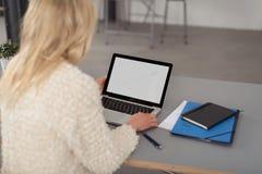 Blonde Frau, die an einer Laptop-Computer arbeitet Stockbilder