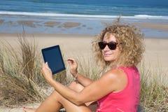 Blonde Frau, die elektronische Tablette am Strand verwendet Lizenzfreie Stockfotos