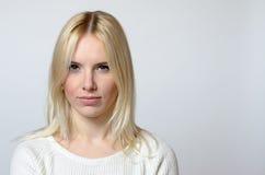 Blonde Frau, die entlang der Kamera gegen Grau anstarrt Stockbild