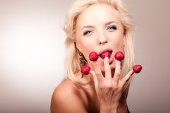 Blonde Frau, die Erdbeere von isst Lizenzfreie Stockbilder