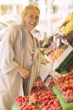 Blonde Frau, die Erdbeeren auf Fruchtstand betrachtet Stockbilder