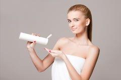 Blonde Frau, die Feuchtigkeitscreme verwendet Stockfotos