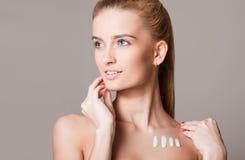 Blonde Frau, die Feuchtigkeitscreme verwendet Stockfoto