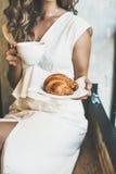 Blonde Frau, die frisches Hörnchen und Schale Cappuccino hält Stockbilder
