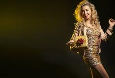 Blonde Frau, die Geburtstagsgeschenk hält Stockfoto