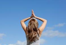 Blonde Frau, die gegen einen blauen Himmel meditiert Stockfotografie