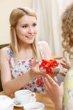 Blonde Frau, die Geschenk im Café gibt Stockbilder