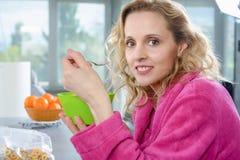 Blonde Frau, die Getreide, am Morgen isst Lizenzfreie Stockbilder