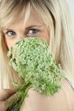 Blonde Frau, die grüne Blume hält Stockfotografie