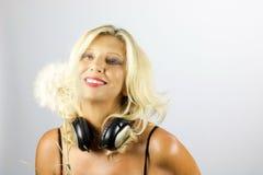 Blonde Frau, die großen Löwenzahn schauend lächelt Stockbilder