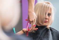 Blonde Frau, die Haar-Schnitt erhält Lizenzfreies Stockfoto