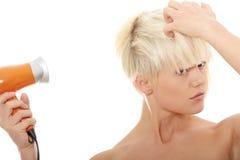 Blonde Frau, die Haartrockner verwendet Lizenzfreies Stockfoto