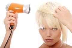 Blonde Frau, die Haartrockner verwendet Lizenzfreie Stockfotografie