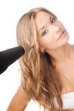 Blonde Frau, die hairdryer anhält Lizenzfreie Stockfotos