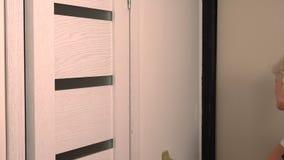 Blonde Frau, die herauf eine Wand mit einem Pinsel sich berührt stock footage