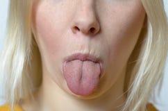 Blonde Frau, die heraus ihre Zunge haftet Stockfotografie