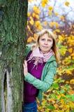 Blonde Frau, die heraus vom Baum schaut Lizenzfreies Stockbild