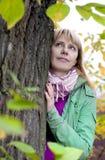 Blonde Frau, die heraus vom Baum schaut Stockfotografie