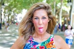 Blonde Frau, die heraus Zunge haftet Lizenzfreies Stockbild