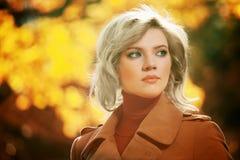 Blonde Frau, die in Herbstwald geht Stockfotografie