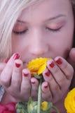 Blonde Frau, die hinter colorfoul Blumen sich versteckt Stockfotos