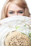 Blonde Frau, die hinter Hut schaut Stockbild