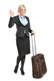 Blonde Frau, die ihr Gepäck und g trägt Lizenzfreies Stockfoto