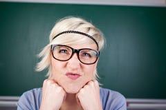 Blonde Frau, die ihr Gesicht gegen Tafel Verzerrt Lizenzfreies Stockfoto
