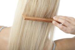 Blonde Frau, die ihr Haar aufträgt Stockbild