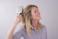 Blonde Frau, die ihr Haar bürstet Lizenzfreie Stockfotografie
