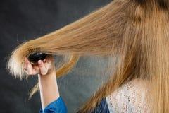 Blonde Frau, die ihr Haar kämmt Stockfotos