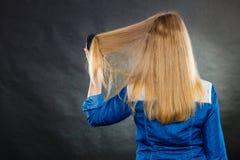 Blonde Frau, die ihr Haar kämmt Stockfotografie
