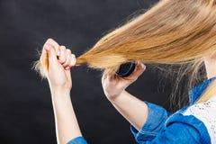 Blonde Frau, die ihr Haar kämmt Lizenzfreie Stockfotos