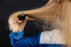 Blonde Frau, die ihr Haar kämmt Lizenzfreie Stockfotografie